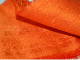 Orange dupioni silk or raw silk fabric made from pure silk yarn